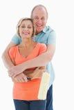 拿着漆滚筒的愉快的更旧的夫妇 图库摄影