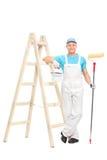 拿着漆滚筒的男性房屋油漆工 库存照片