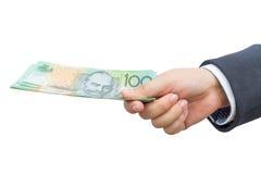 拿着澳大利亚元(AUD)在被隔绝的背景的商人手 免版税库存照片