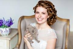 拿着灰色k的婚礼礼服的美丽的愉快的微笑的女孩 库存照片