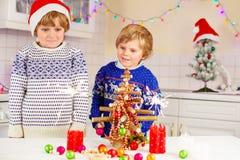 拿着灼烧的闪烁发光物的两个小孩 库存照片