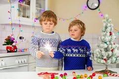 拿着灼烧的闪烁发光物的两个小孩 免版税库存照片