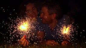 拿着灼烧的闪烁发光物的愉快的年轻夫妇在晚上 超级慢动作500 fps 股票录像