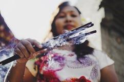 拿着灼烧的香火棍子的美丽的巴厘语妇女 免版税库存照片