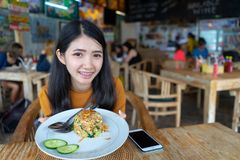 拿着炒米在桌上的女性手板材mealÂ在有人群人的餐馆在背景中 年轻亚洲妇女吃泰语 免版税库存照片