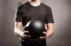 拿着炸弹的年轻人 免版税库存照片