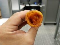拿着炸鸡在办公室设置的手炸玉米饼垃圾食品 免版税图库摄影