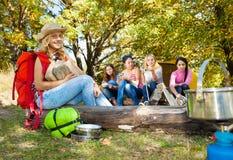 拿着点燃木头的白肤金发的女孩坐日志 免版税库存照片