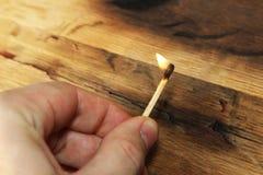 拿着点燃的火柴的一只白种人手 这个图象也包含木背景,并且可以使用代表火开始或a 免版税库存照片
