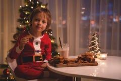 拿着烘烤的盘子用姜曲奇饼和微笑对照相机的圣诞老人帽子的可爱的愉快的男孩 免版税库存图片