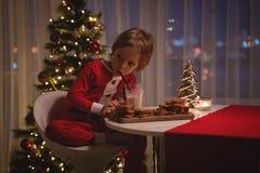 拿着烘烤的盘子用姜曲奇饼和微笑对照相机的圣诞老人帽子的可爱的愉快的男孩 库存照片
