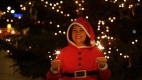拿着烟花,圣诞节概念的红色毛线衣的愉快的妇女 股票录像