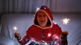拿着烟花,圣诞节概念的红色毛线衣的愉快的阿曼 股票录像