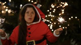 拿着烟花,圣诞节概念的红色毛线衣的愉快的阿曼 股票视频