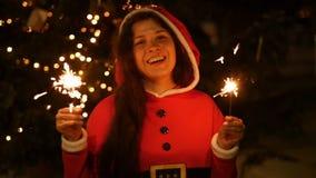 拿着烟花,圣诞节概念的红色毛线衣的愉快的阿曼 影视素材