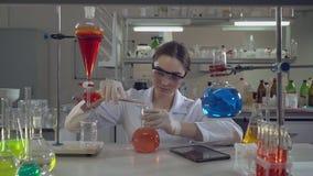 拿着烧瓶的可爱的专业科学家在实验室 股票录像