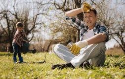 拿着热杯子的疲乏的男性收养,当有草时的基于 免版税库存照片