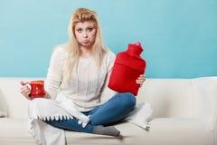 拿着热水袋和茶在杯子的妇女 免版税图库摄影