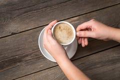 拿着热的咖啡的妇女手 从上面的看法在一个温暖的咖啡杯 库存图片