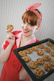 拿着热的烧烤平底锅用巧克力曲奇饼的美丽的妇女 免版税库存图片