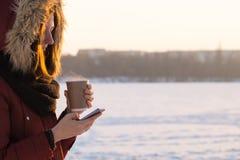 拿着热的饮料和使用智能手机户外在冬天 库存照片