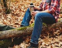 拿着热水瓶和茶的远足者人在森林里 免版税库存图片