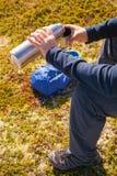 拿着热水瓶用热的茶的人户外 远足和休闲 图库摄影