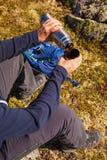 拿着热水瓶用热的茶的人户外 远足和休闲 库存图片