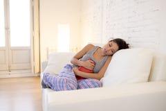 拿着热水袋的年轻美丽的西班牙妇女反对遭受月经痛苦的腹部 免版税库存图片