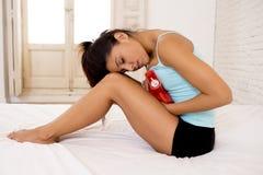 拿着热水袋的年轻美丽的西班牙妇女反对遭受月经痛苦的腹部 库存图片