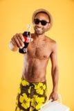 拿着焦炭瓶的帽子和太阳镜的快乐的年轻人 免版税库存照片