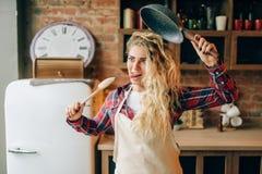 拿着煎锅和木小铲的主妇 免版税库存图片