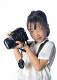 拿着照片照相机的亚裔小女孩画象  免版税库存图片