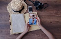 拿着照片的女孩的手一个册页与照相机, p 图库摄影