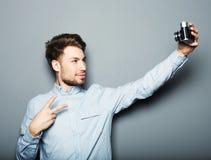 拿着照相机和做selfie的英俊的年轻人 库存图片