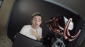 拿着照相机用他的手和记录一本证明书的男性vlogger在关于他的前假期经验的一个演播室- 股票录像