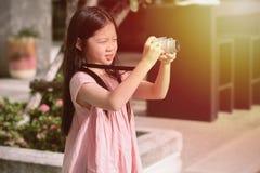 拿着照相机的亚裔孩子拍照片 免版税库存照片