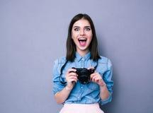 拿着照相机的惊奇年轻俏丽的妇女 免版税库存图片