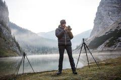 拿着照相机的摄影师,检查照片 库存图片