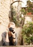 拿着照相机的年轻旅客妇女 库存图片