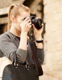 拿着照相机的年轻旅客妇女 图库摄影