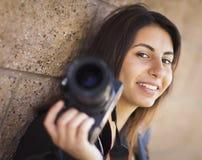 拿着照相机的混合的族种年轻成年女性摄影师 免版税库存图片