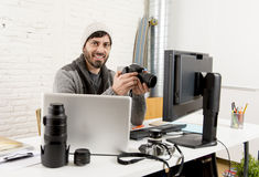 拿着照相机的年轻可爱的摄影记者观看他的在编辑办公室书桌上的工作 免版税库存照片
