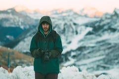 拿着照相机,多雪的山的英俊的有胡子的年轻人在背景中 库存图片