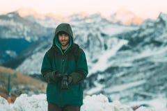 拿着照相机,多雪的山的英俊的有胡子的年轻人在背景中 免版税图库摄影