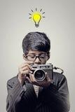 拿着照相机-想法电灯泡的儿童摄影师 免版税库存照片