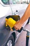 拿着燃料喷嘴的手增加气体 免版税库存图片
