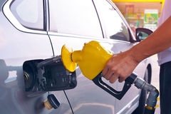 拿着燃料喷嘴的手增加气体 库存图片