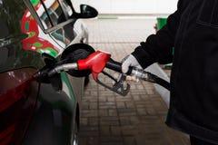 拿着燃油泵和重新装满汽车的手特写镜头照片在加油站 库存图片
