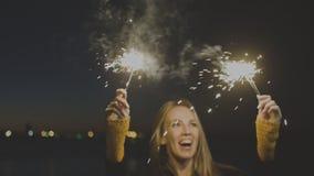 拿着燃烧的闪烁发光物的妇女 在手中举行两个闪烁发光物室外庆祝的新年s前夕的Overhappy年轻女人 股票视频